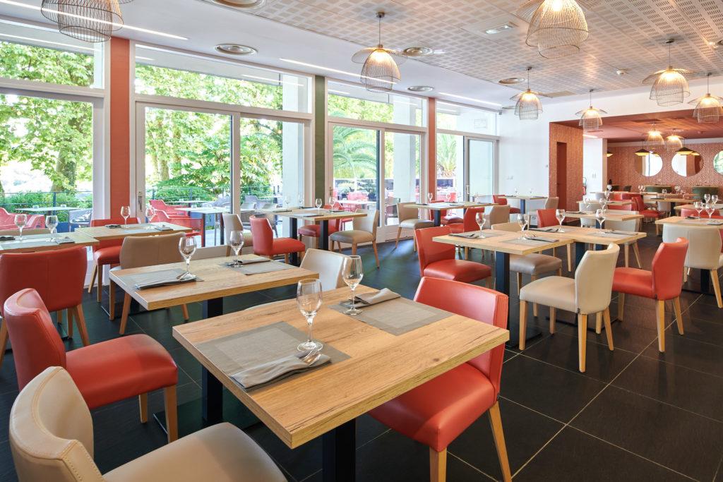 Salle de restaurant avec une décoration terracota et touches de vert à Bayonne